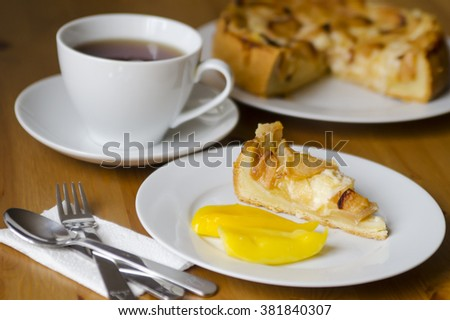 Table served to tea drinking. White cup of tea, paper napkin, cutlery and apple homemade pei  on the wooden table. - stock photo