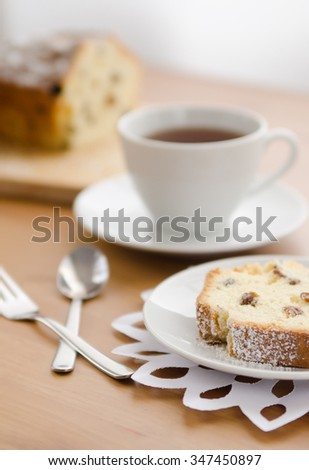 Table served to tea drinking. White cup of tea, paper napkin, cutlery and cake with raisins on the wooden table. - stock photo