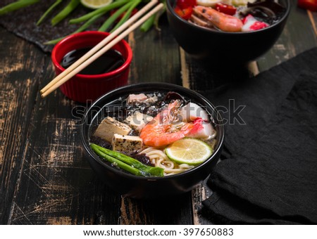 Table served with asian noodle soup in a black bowls with chopsticks, soy sauce, sliced lime and ginger on a dark textured wooden background. Asian style dinner. Close up. Selective focus - stock photo