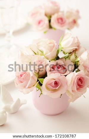 Table set for an event party or wedding reception - fresh rose flowers in vase - stock photo