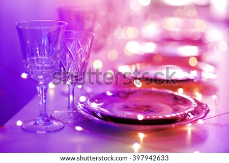 Table set for an event party or wedding reception in orange light - stock photo