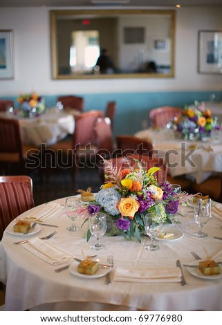 Table set for an event party or wedding reception, shallow DOF focus on centerpiece bouquet - stock photo