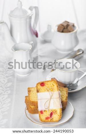 Table set for breakfast with candied fruit cake, tea and coffee - stock photo