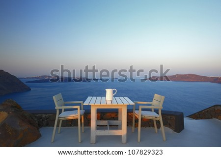 table set on the cliff of Santorini, Greece - stock photo