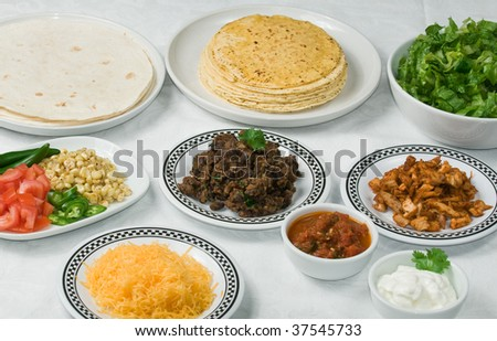 Table set with mexican ingredients for taco or burrito dinner - stock photo