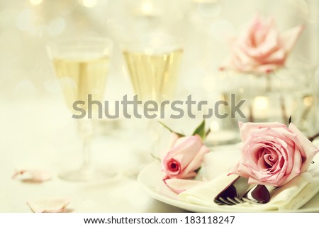 Table setting and glasses with pink roses  - stock photo
