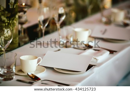 Table setting at wedding. Steampunk style. Glasses. plates, cutlery on craft paper with candlelights on background. - stock photo