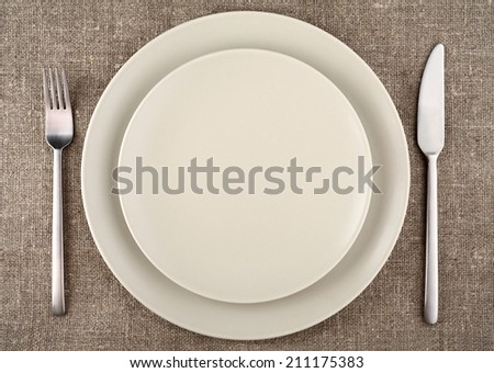 Table setting. Beige plate, fork, knife and beige linen tablecloth. - stock photo