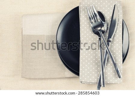 Table setting: black plate, fork and knife with napkins on linen tablecloth. Top view point. Toned image. - stock photo