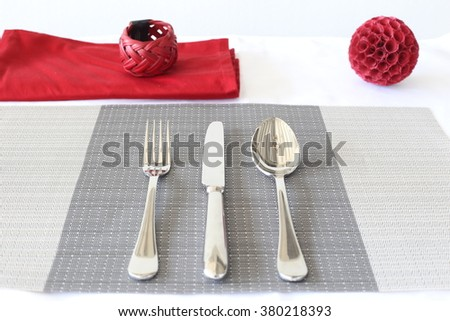 Table setting. Cutlery, fork, spoon, knife on a plate mat  decorated with red ball.  - stock photo