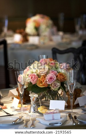 table setting for a wedding or dinner event, very shallow depth of field with the focus on the flowers, blurry background. - stock photo