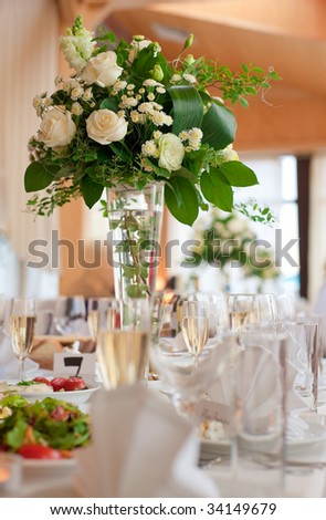 Table setting for a wedding or dinner event, with flowers in vase of glass - stock photo