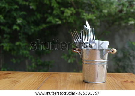 Table setting. Forks, knifes and spoons in vintage style zinc cutlery holder, Set on wooden table. - stock photo