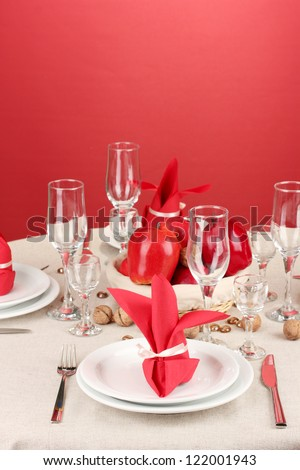 Table setting in red tones on color  background - stock photo