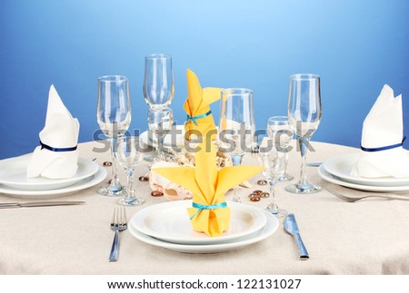 Table setting in white and yellow tones on color  background - stock photo