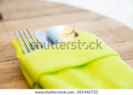 table setting, silverware and eating concept - close up of cutlery set wrapped to napkin on restaurant table - stock photo