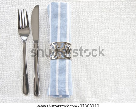 Table setting with blue and white striped napkin and knife and fork with space for text - stock photo