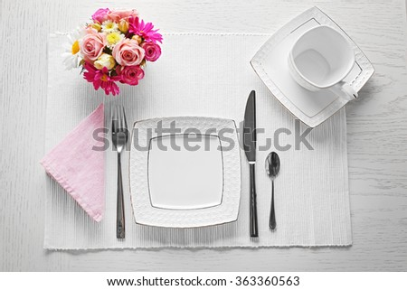 Table setting with dishes, cutlery and flowers on white background - stock photo