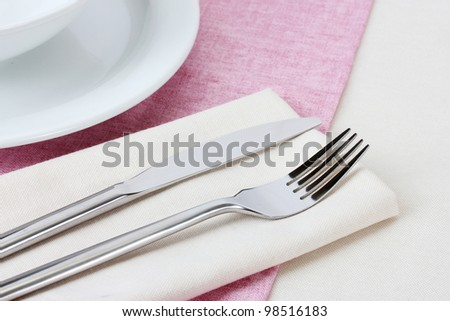 Table setting with fork, knife, plates and napkin - stock photo