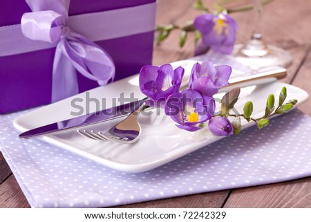 table setting with gift and flowers - stock photo