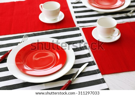 Table setting with red and striped napkins - stock photo
