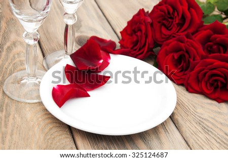 Table setting with red roses and petals on a plate - stock photo