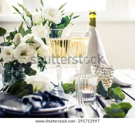 Table setting with white flowers, candles and glasses of champagne on an old vintage rustic wooden table. Vintage summer wedding table decoration. - stock photo