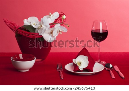 Table setting with white orchid flowers on red tablecloth on red background - stock photo