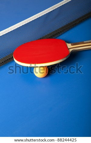 Table tennis or ping pong rackets and balls on a blue table - stock photo