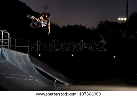 Table top in a skatepark, bmx bike trick on a quarter pipe - stock photo