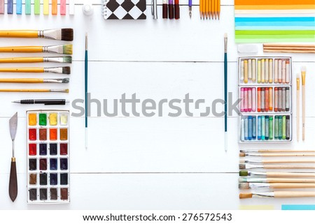 Table top view of the artist. On the table are perfectly paints, brushes, crayons and stationery items designed for easy operation. - stock photo