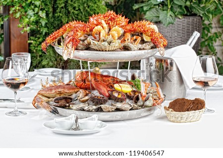 table with a bottle of wine, seafood and wine glasses - stock photo