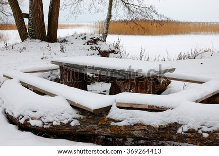 table with benches for picnic under snow on the bank of the winter lake - stock photo