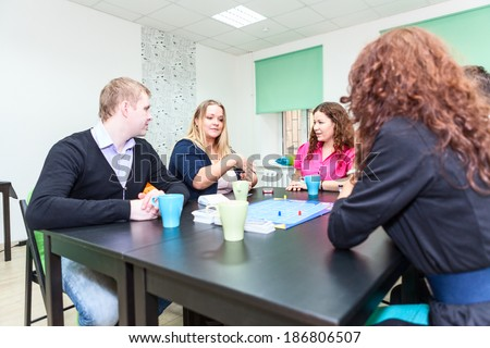 Table with board game and funny young adults playing - stock photo