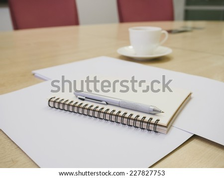 Table with book blank paper pen and coffee in meeting room office - stock photo