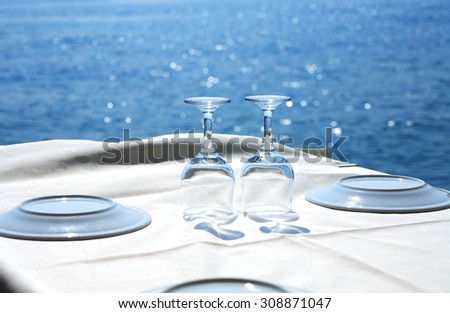 Table with empty wineglasses and plates near blue sea under sunlight - stock photo