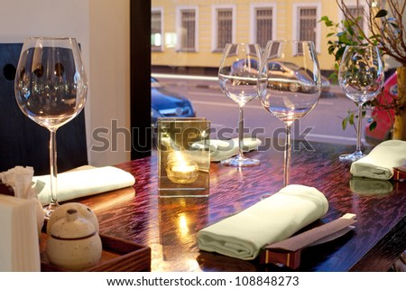 Table with glasses, candle, towels, sticks, with view on street - stock photo