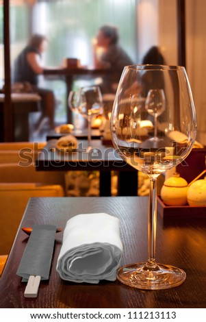 table with glasses, towel, sticks in sushi bar, couple sitting by window - stock photo