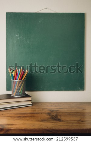 Table with pencils and stack of books - stock photo