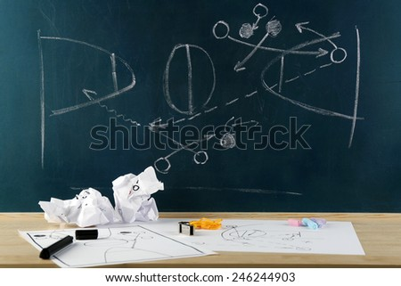 Table with sheets of paper and blackboard with scheme basketball game on background - stock photo