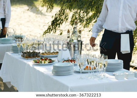 Table with snacks, crockery and bottles of champagne and wine outdoors to celebrate the solemn event. Waiters around banquet tables - stock photo