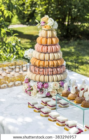 table with sweets decorated with flowers and macaroon cake - stock photo