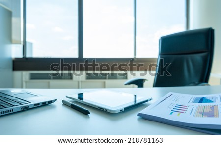 table work in empty office room of manager with tablet and report with laptop - stock photo