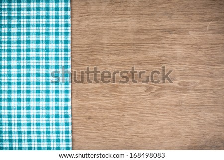 Tablecloth and wooden table background - stock photo
