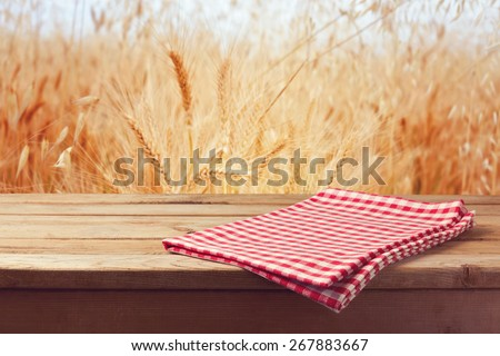 Tablecloth on wooden table over wheat field - stock photo