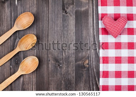 Tablecloth textile, spoons, heart on wooden table background - stock photo