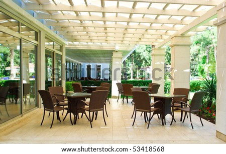 Tables and armchairs on terrace in street cafe - stock photo