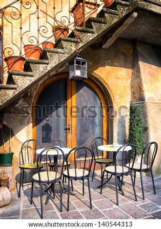 tables and chairs at a bistro in italy - stock photo