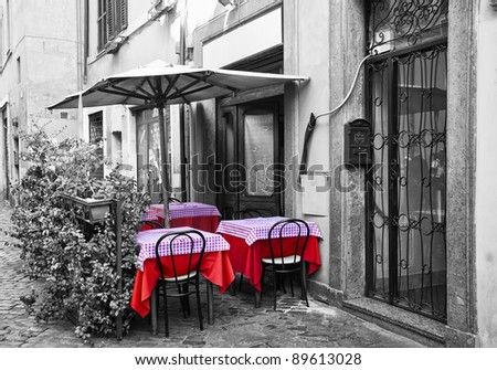 Tables and chairs for a restaurant in one of the streets of Trastevere.  In black and white and selective de-saturation - stock photo