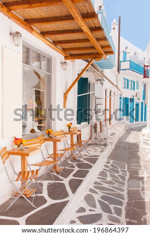 Tables and  chairs in a cafe near the hotel on the island of Mykonos - stock photo